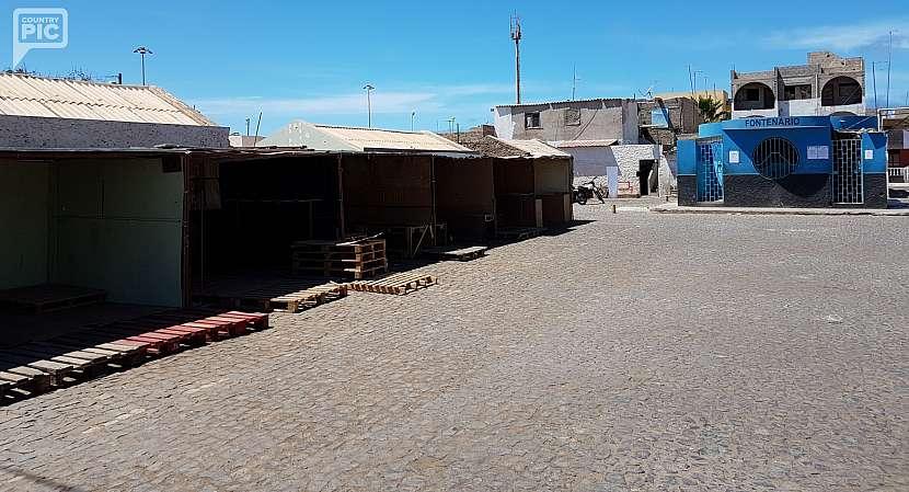Místní trh a vpravo zásobárna pitné vody.